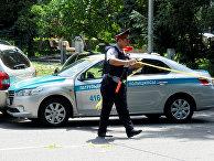 Полицейский огораживает место преступления на улице в Алма-Ате