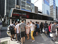 Китайские туристы ждут в очереди в автобус в Токио