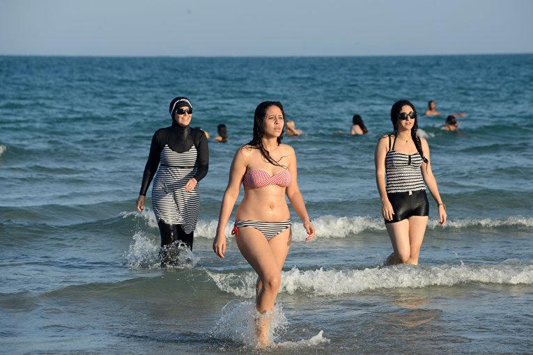 Девушки в буркини и бикини на пляже в Тунисе