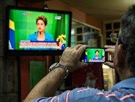 Мужчина записывает выступление по бразильскому телевидению временно отстраненной от должности Дилмы Роуссефф