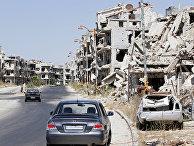 Поврежденные здания и автомобили в Хомсе