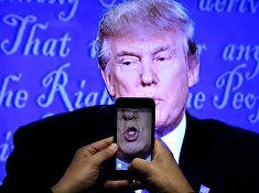 Журналист записывает видео с экрана во время дебатов между Дональдом Трампом и Хиллари Клинтон