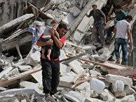 Мужчина несет раненого ребенка после авиаударов в Алеппо