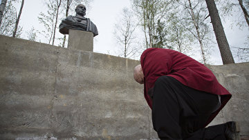 Мужчина кланяется бюсту российского президента Владимира Путина