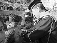 Визит советских кораблей в Сирийскую Арабскую Республику. Советский моряк дарит значки сирийским детям