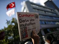 Протестующий с выпуском Cumhuriyet рядом с офисом редакции газеты в Стамбуле, заголовок на первой полосе: «Новый рейд против оппозиции»