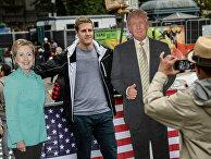 Мужчина фотографируется с ростовыми фигурами кандидатов в президенты США