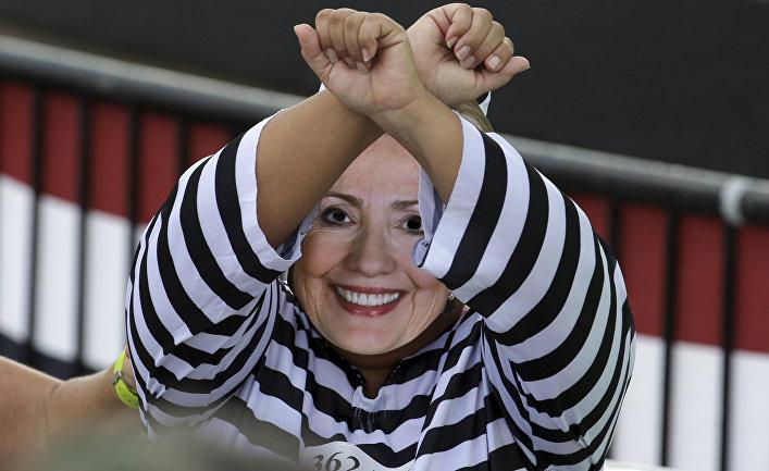 Человек в маске Хиллари Клинтон на митинге в поддержку кандидата в президенты США Дональда Трампа