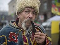 Мужчина в национальном костюме курит трубку на площади Независимости в Киеве