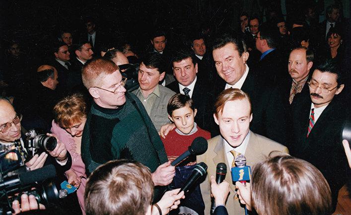 Руслан Пономарев дает интервью после ЧМ по шахматам 2002 года. Сзади в красном свитере стоит Сергей Карякин, рядом Виктор Янукович