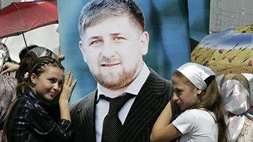 Девушки стоят рядом с портретом Рамзана Кадырова в Грозном
