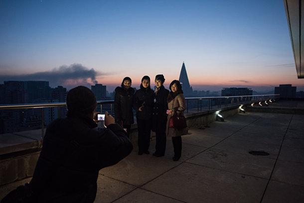 Туристы позируют для фото на вершине Триумфальной арки в Пхеньяне