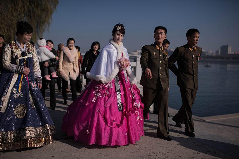 Жених и невеста с родственниками и друзьями ругяют на берегу реки Тэдон в Пхеньяне