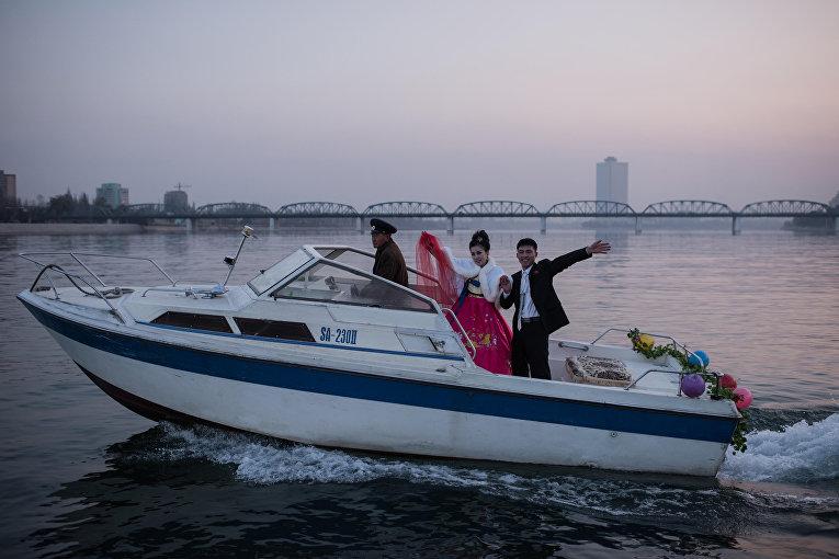 Жених и невеста на борту лодки на реке Тэдон в Пхеньяне