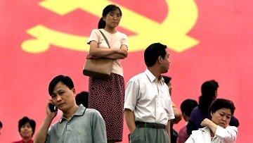 Пекинцы на фоне партийного флага