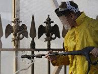 Работник чистит забор с бронзовыми скульптурами двуглавых орлов государственного герба России