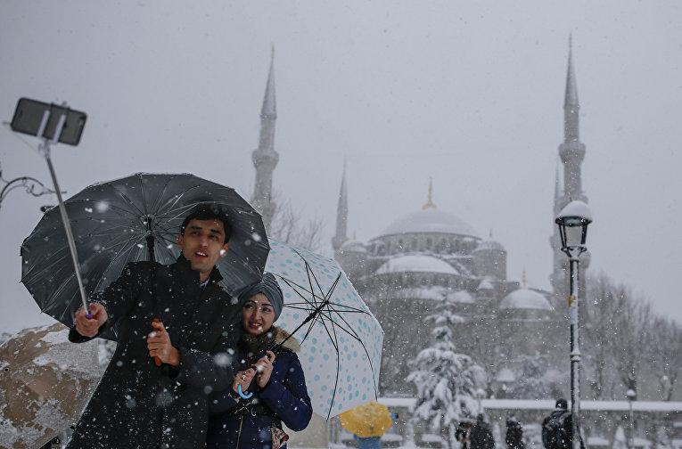 Парочка делает селфи на фоне заснеженного Собора Святой Софии в Стамбуле