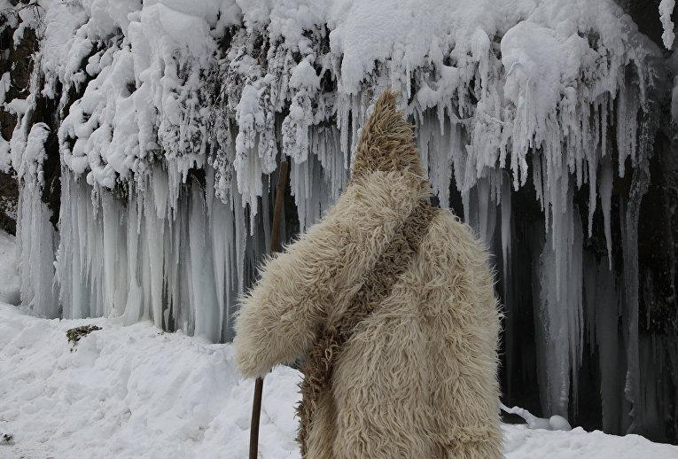 Местный житель на фоне замершего водопада в Косово