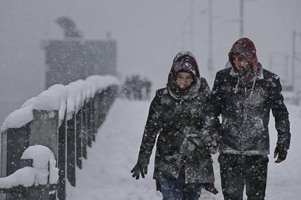 Сильный снегопад на мосту Золотой Рог в Стамбуле