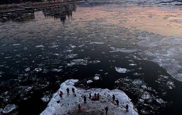Люди фотографируют льдины в водах Дуная в центре Будапешта