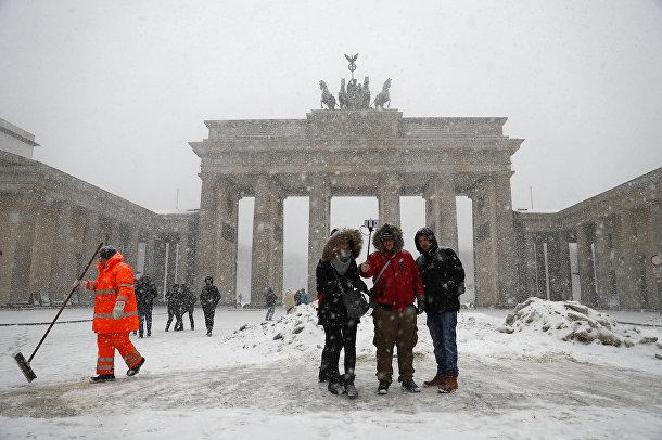 Туристы фотографируются возле Бранденбургских ворот в Берлине