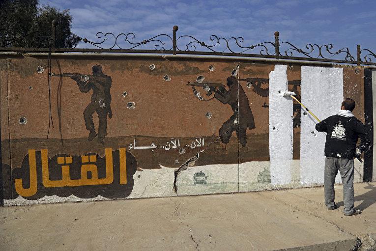 Доброволец на востоке Мосула закрашивает пропагандистский лозунг ИГИЛ