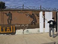 Волонтер закрашивает граффити, оставленное ИГИЛ в Мосуле