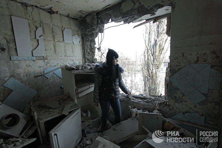 Девушка в квартире, разрушенной от попадание снаряда в результате обстрела, в Киевском районе Донецка