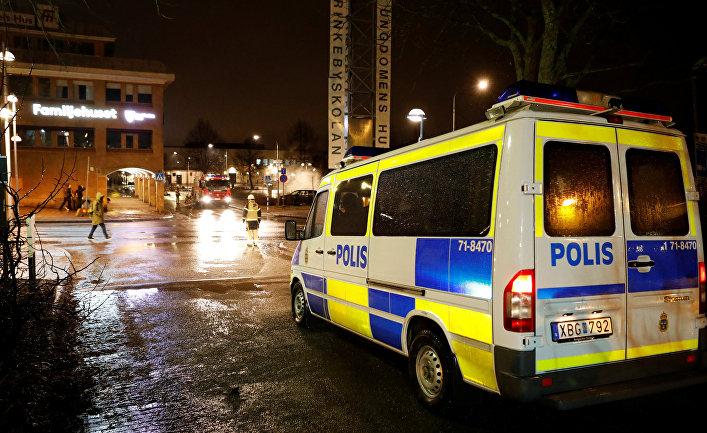Полицейский автомобиль во время беспорядков в пригороде Стокгольма