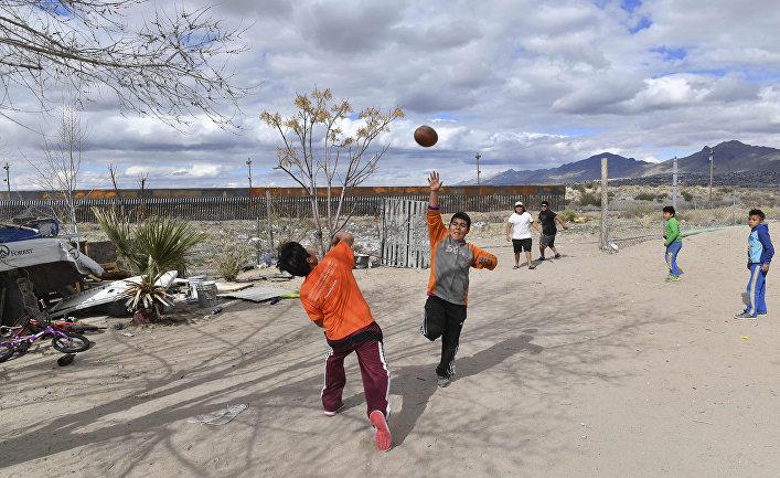 Мексиканские дети играют в Пуэрто Анапре, неподалеку от пограничной стены