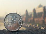 Рублевая монета на фоне Московского Кремля