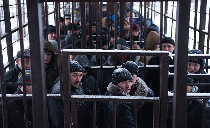 Мигранты из стран ближнего зарубежья стоят в очереди в одном из отделений УФМС по городу Москве