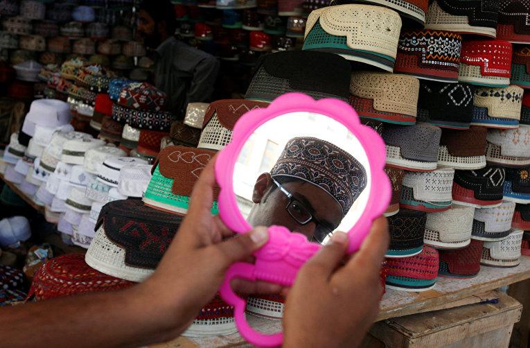 Мальчик примеряет кепку в лавке около мечети перед началом Рамадана