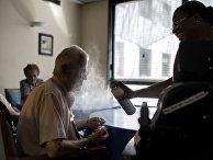 Медсестра помогает пожилому пациенту справиться с аномально жаркой погодой в Лионе