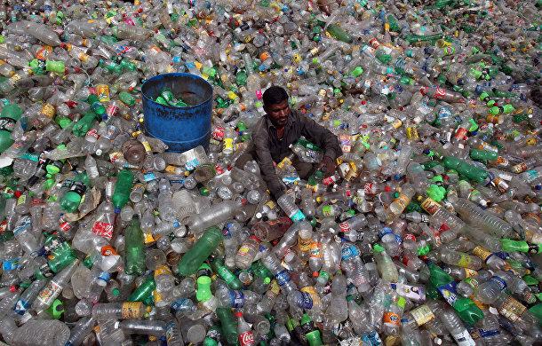 Мужчина сортирует пластиковые бутылки на свалке в Чандигарха, Индия