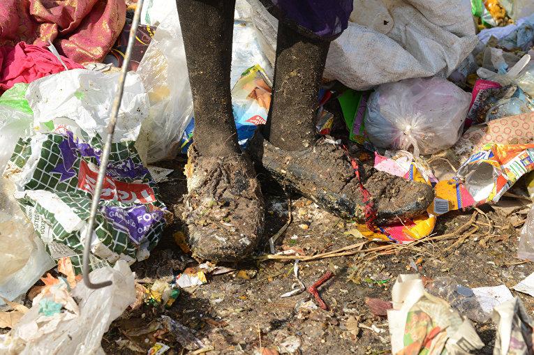 Ноги девушки, которая собирает материалы для переработки мусора на свалке в Индии