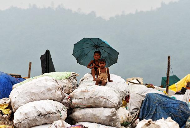 Дети на мешках с мусором, предназначенным для переработки в Гувахати, Индия