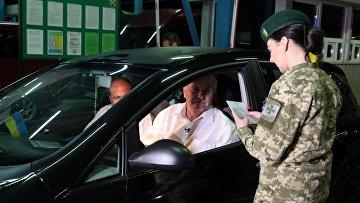 Сотрудница пограничной службы Украины проверяет документы на международном пункте пропуска через украинско-польскую границу
