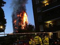 Сотрудники полиции на месте пожара в многоэтажном доме Grenfell Tower в Лондоне. 14 июня 2017