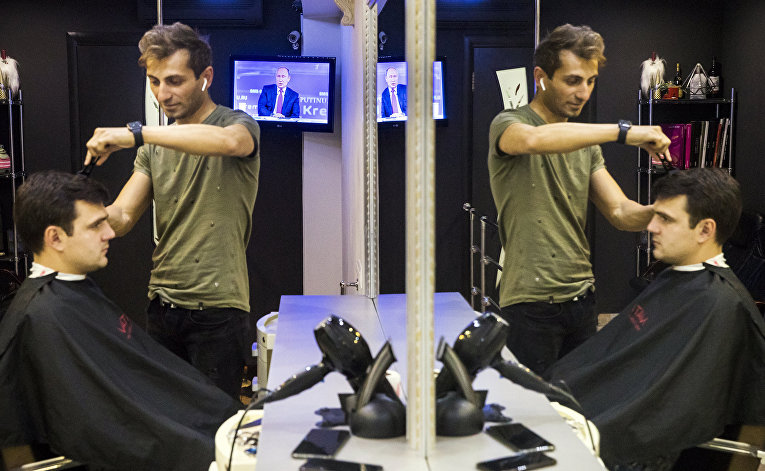 Клиент парикмахерской в Москве смотрит «прямую линию» во время стрижки
