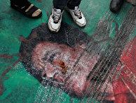 Лежащий на земле портрет Муамара Каддафи