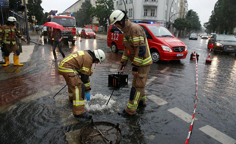 Сотрудники пожарной инспекции работают на затопленной улице в Берлине