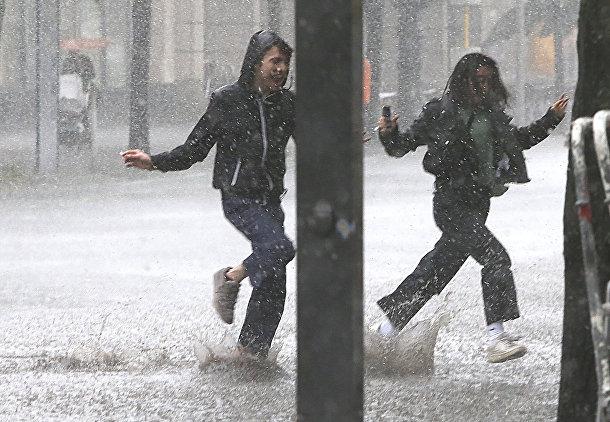 Люди во время сильнейшего ливня в Берлине
