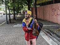 Оппозиционный активист Вилли Артеаги показывает сломанную скрипку во время акции протеста в Каракасе