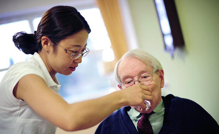 Медсетра ухаживает за постояльцем в доме для престарелых во Франкфурте-на-Майне, Германия
