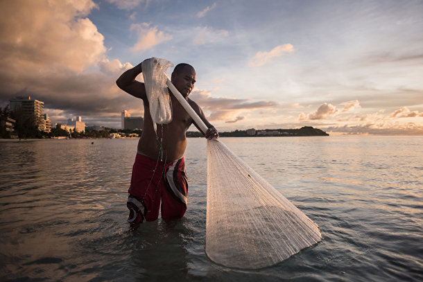 Рыбак ловит рыбу на пляже в заливе Тумон.