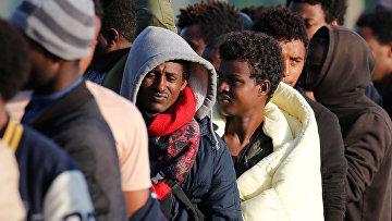 Мигранты из Эфиопии и Эритреи во время распределения продовольствия в Кале
