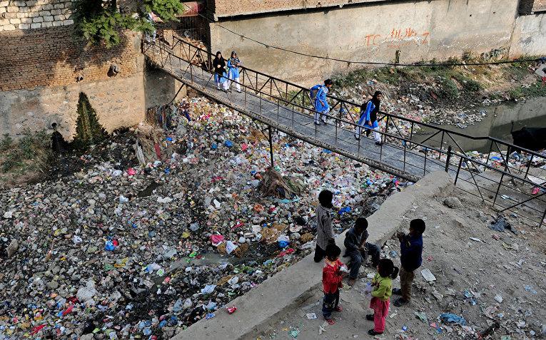 Ученики спешат в школу по подвесному мосту в трущебах Равалпинди