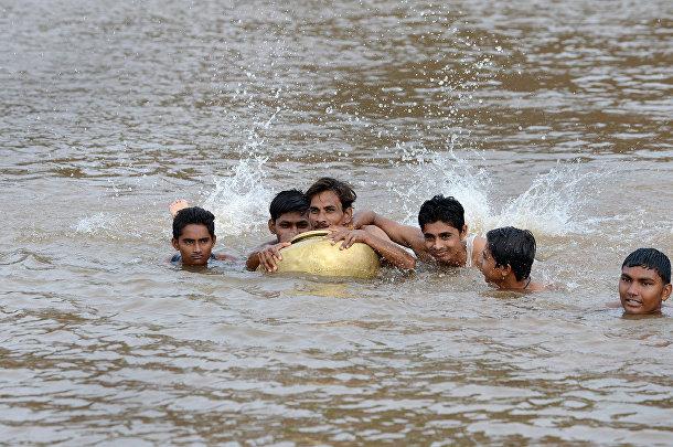 Школьники из индийской деревни Саджанпура переплывают реку Хиран