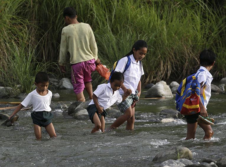 Школьникам из филиппинской деревни приходится переходить реку вброд на пути в школу